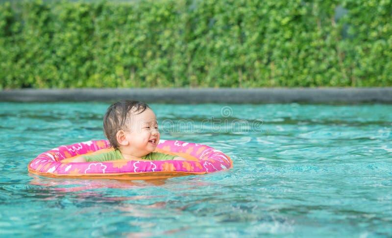 Primo piano che un neonato si siede in una barca per i bambini nei precedenti della piscina con il fronte di sorriso nell'emozion immagine stock
