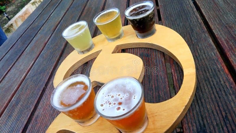 Primo piano con i vetri con differenti specie della birra del mestiere sulla tavola di legno fotografia stock libera da diritti