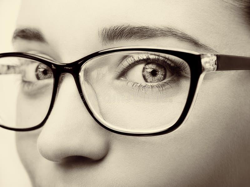 Primo piano d'uso di vetro della bella giovane donna su fondo bianco immagini stock libere da diritti