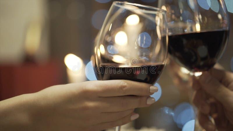 Primo piano degli amici vetri tintinnanti del champagne e del vino rosso nel ristorante azione Riunione del ` s dell'amico immagine stock