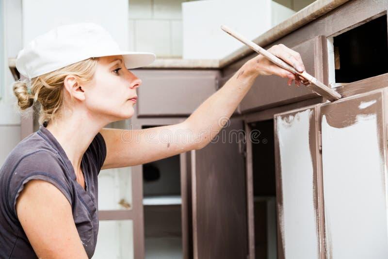 Primo piano degli armadi da cucina della pittura della donna immagini stock libere da diritti