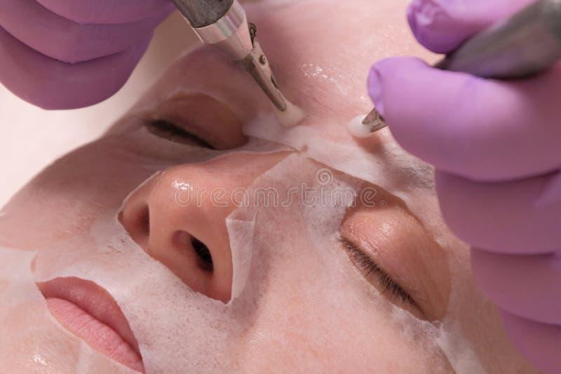 Primo piano degli elettrodi nelle mani di un estetista, toccanti la guancia femminile attraverso una maschera Donna che riceve st immagine stock libera da diritti