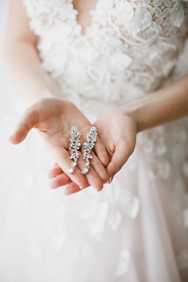 Primo piano degli orecchini nelle mani della sposa Accessori dei gioielli fotografia stock