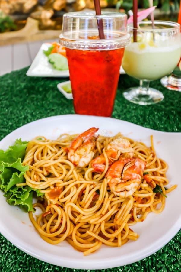Primo piano degli spaghetti con il gamberetto piccante sul piatto bianco e sul tè ghiacciato del limone immagini stock libere da diritti