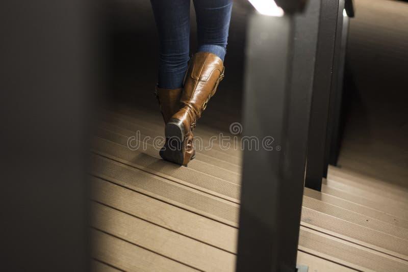 Primo piano degli stivali di cuoio della donna sulle scale fotografia stock libera da diritti