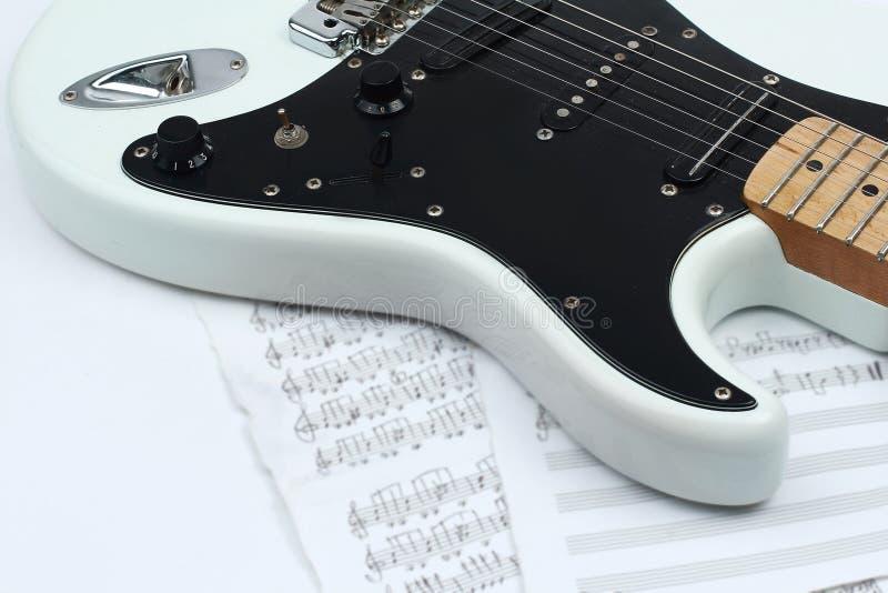 Primo piano degli strati di musica e della chitarra elettrica in bianco e nero Iso immagine stock