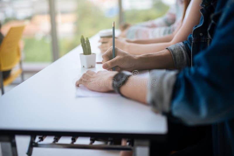 Primo piano degli studenti delle mani che si siedono sulla conferenza e che hanno scrittura della matita della tenuta della prova fotografia stock