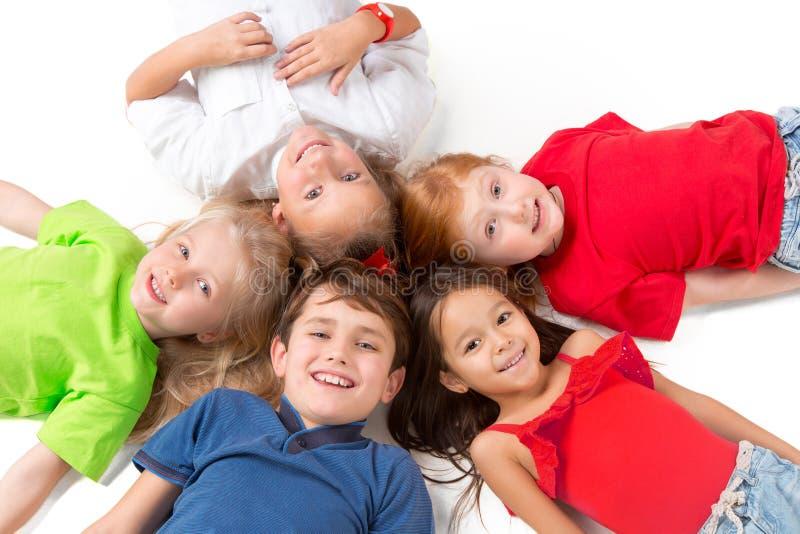 Primo piano dei bambini felici che si trovano sul pavimento in studio e nel cercare fotografia stock