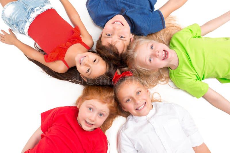 Primo piano dei bambini felici che si trovano sul pavimento in studio e nel cercare immagini stock