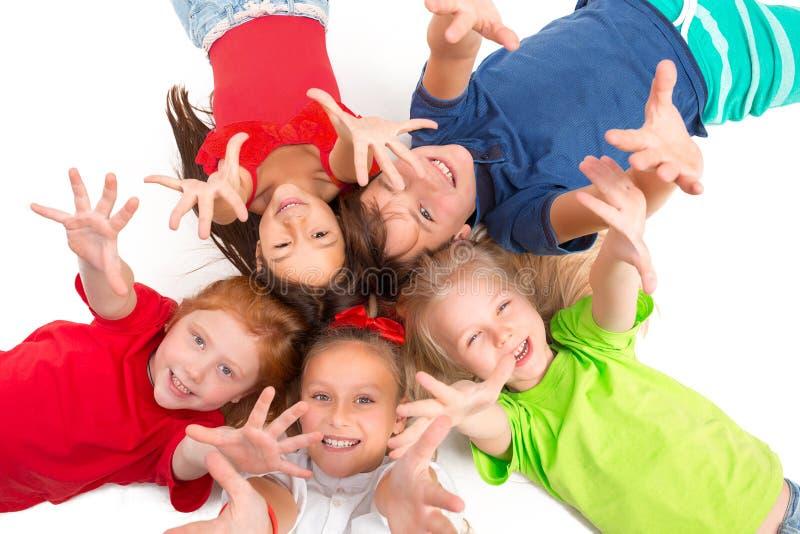 Primo piano dei bambini felici che si trovano sul pavimento in studio e nel cercare fotografia stock libera da diritti