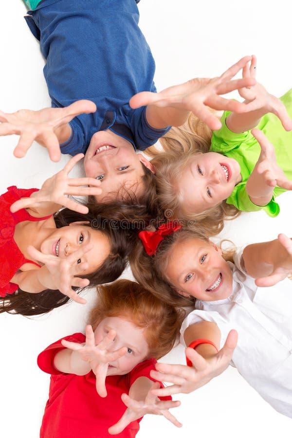 Primo piano dei bambini felici che si trovano sul pavimento in studio e nel cercare fotografie stock