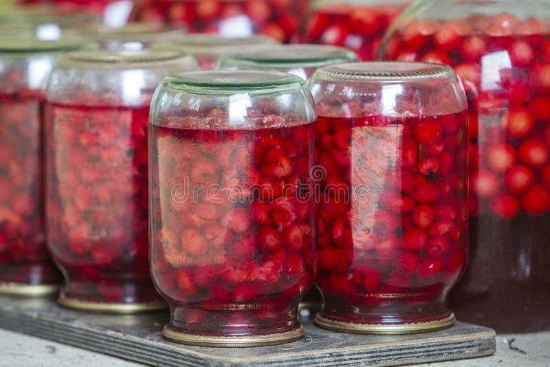 Primo piano dei barattoli di vetro con le ciliegie succose rosse mature coperte di coperchi del metallo sottosopra sul piatto di  fotografia stock libera da diritti