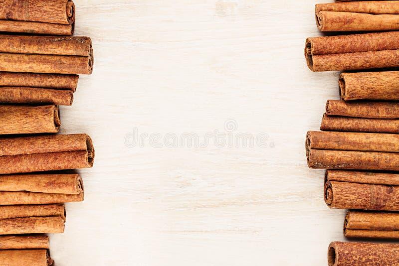 Primo piano dei bastoni di cannella su fondo di legno bianco immagini stock