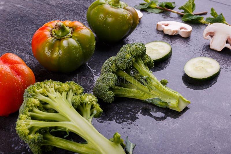 Primo piano dei broccoli e peperone dolce, pezzi di cetriolo e funghi prataioli su un fondo nero fotografie stock libere da diritti