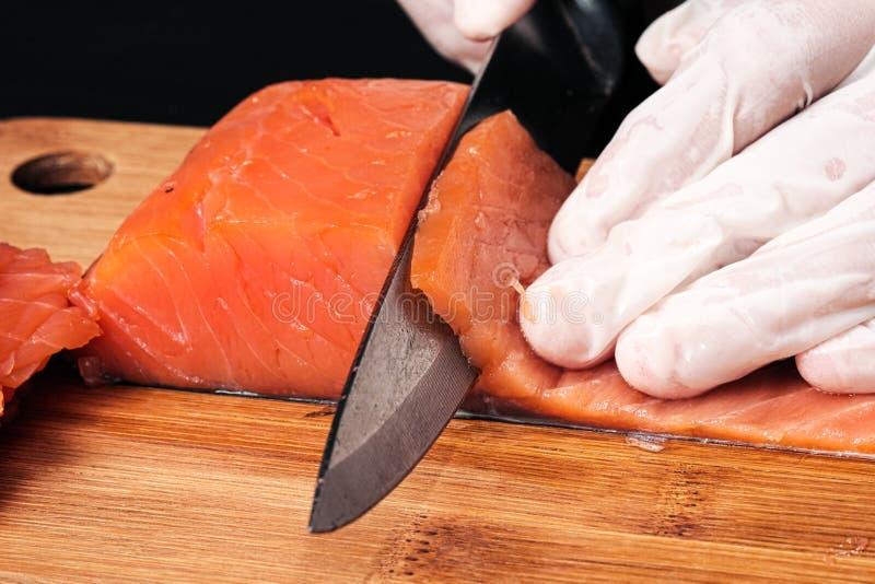 primo piano dei cuochi delle mani Il cuoco unico taglia con un coltello un pesce rosso, salmone affumicato su un tagliere di legn fotografia stock libera da diritti