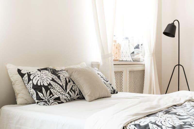 Primo piano dei cuscini e della copertura di motivo della foglia su un letto in un interno luminoso della camera da letto Lampada fotografie stock