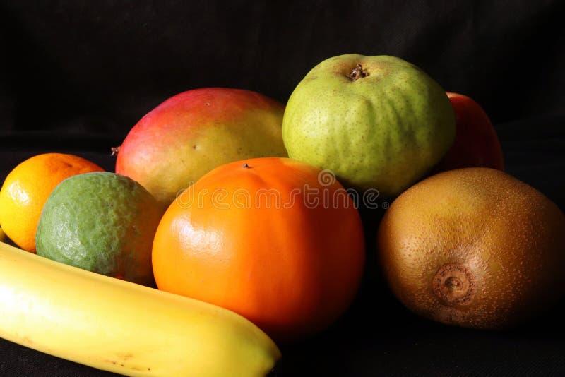 Primo piano dei frutti tropicali contro fondo nero fotografie stock