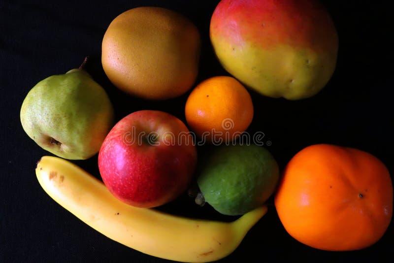 Primo piano dei frutti tropicali contro fondo nero immagini stock libere da diritti