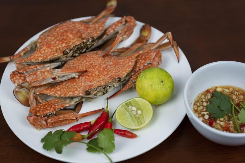 Primo piano dei granchi nuotatori con la salsa di immersione tailandese dei frutti di mare su un piatto fotografia stock libera da diritti