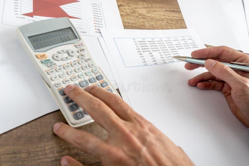 Primo piano dei numeri calcolatori del consulente finanziario maschio fotografia stock libera da diritti