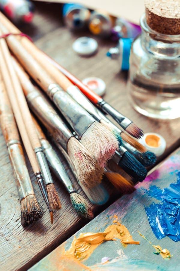 Primo piano dei pennelli, tavolozza dell'artista e tubi multicolori della pittura immagine stock libera da diritti