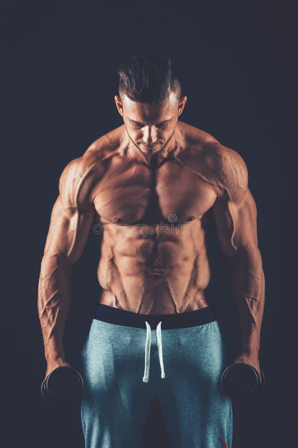 Primo piano dei pesi di sollevamento muscolari delle teste di legno di un giovane su dar immagini stock libere da diritti
