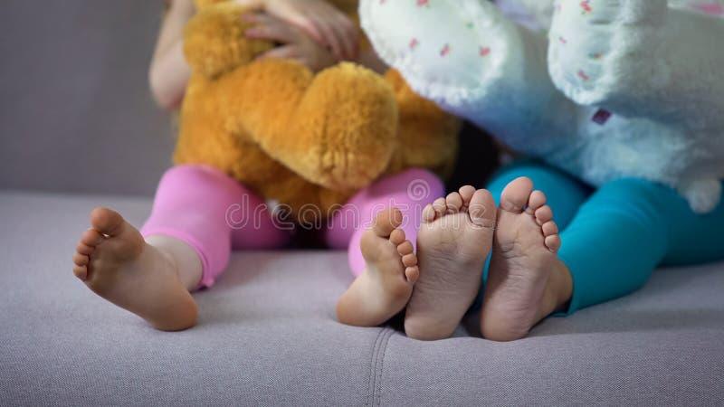 Primo piano dei piedi dei bambini, amici multirazziali che si siedono sul sofà, giocante con gli orsacchiotti immagine stock