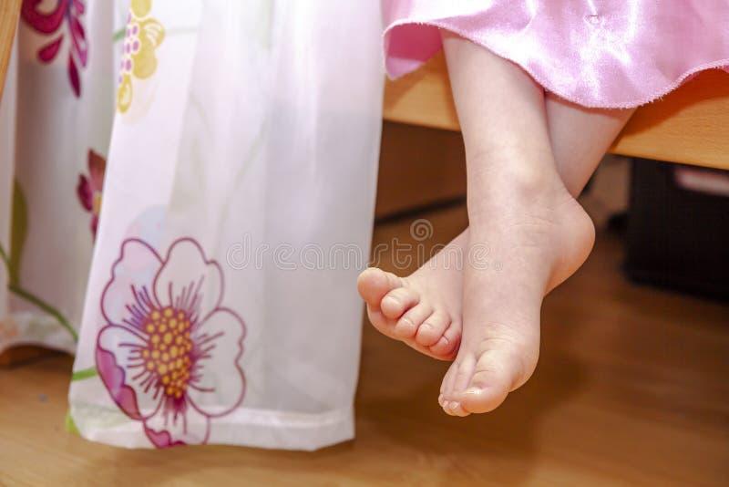 Primo piano dei piedi della bambina mentre sedendosi sul letto fotografia stock