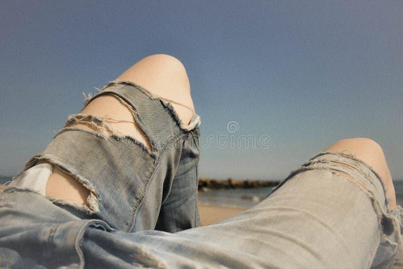 Primo piano dei piedi di una femmina con i jeans lacerati ed il fondo blu di stupore immagini stock