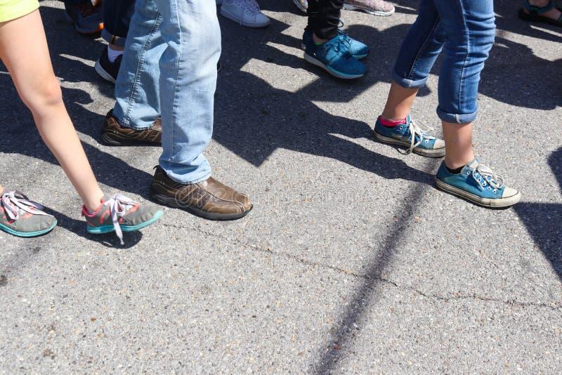 Primo piano dei piedi e delle gambe - la gente che cammina sul marciapiede incrinato con le vari scarpe e pantaloni fotografia stock