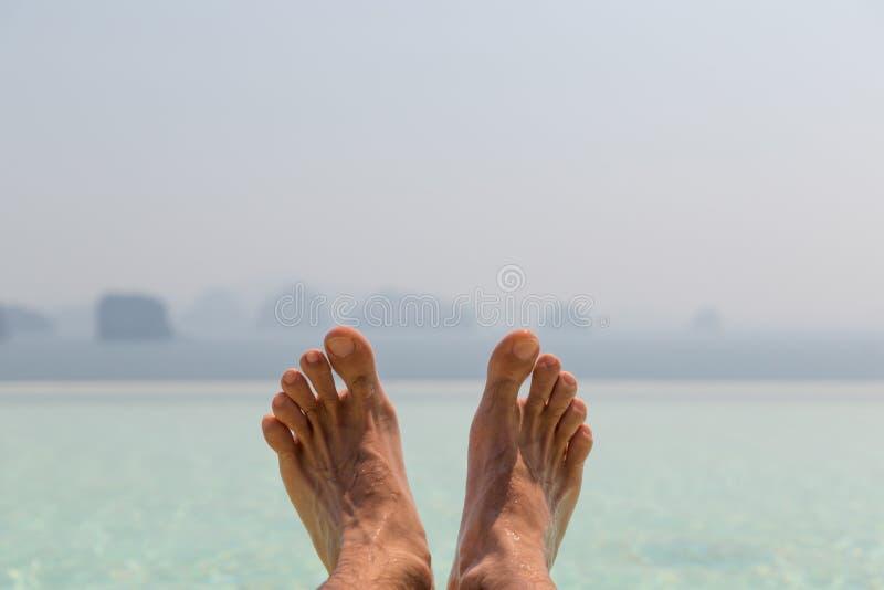 Primo piano dei piedi maschii sopra il mare ed il cielo sulla spiaggia fotografie stock libere da diritti