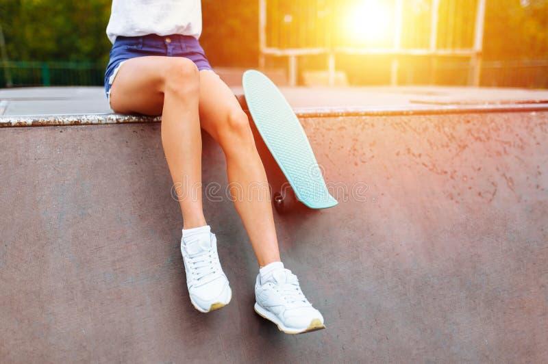 Primo piano dei piedi, ragazza con il pattino nel parco del pattino, al tramonto immagini stock