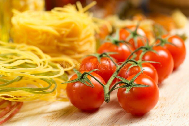 Primo piano dei pomodori ciliegia e della pasta fotografia stock