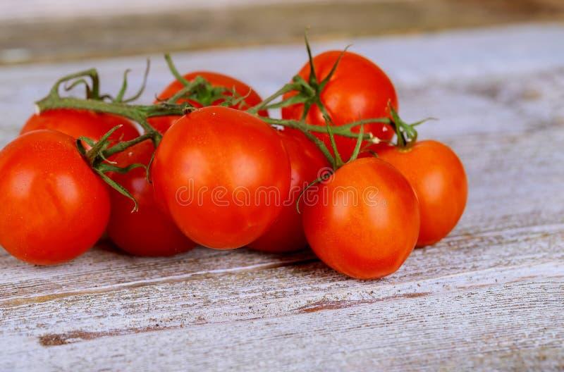 Primo piano dei pomodori ciliegia freschi e maturi su legno fotografia stock