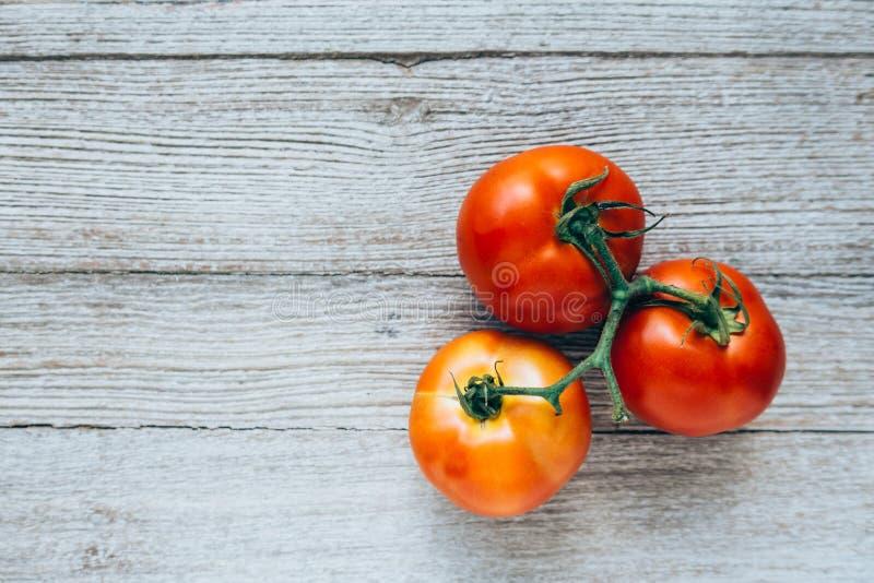 Primo piano dei pomodori freschi e maturi su legno fotografia stock