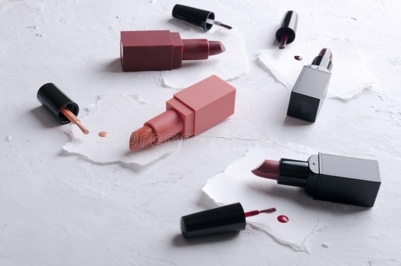 Primo piano dei rossetti aperti, spazzole di smalto su pezzi di carta bianchi immagini stock