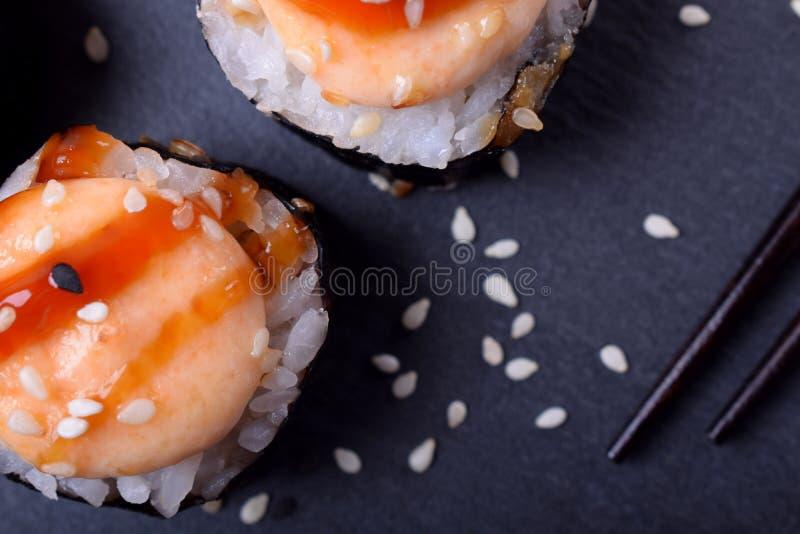 Primo piano dei rotoli di sushi avvolti in nori con salsa piccante immagine stock libera da diritti