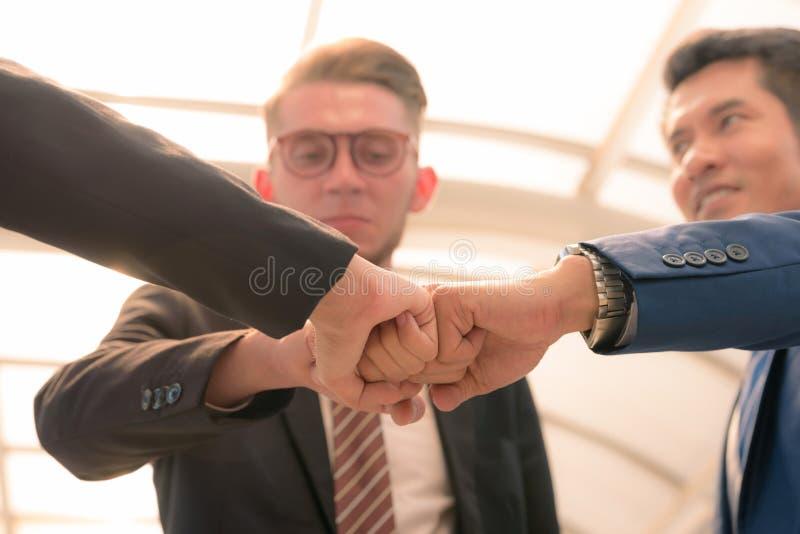 Primo piano dei soci commerciali che fanno mucchio delle mani alla riunione immagini stock libere da diritti