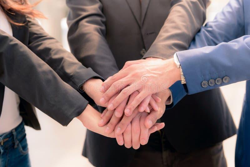 Primo piano dei soci commerciali che fanno mucchio delle mani alla riunione immagini stock