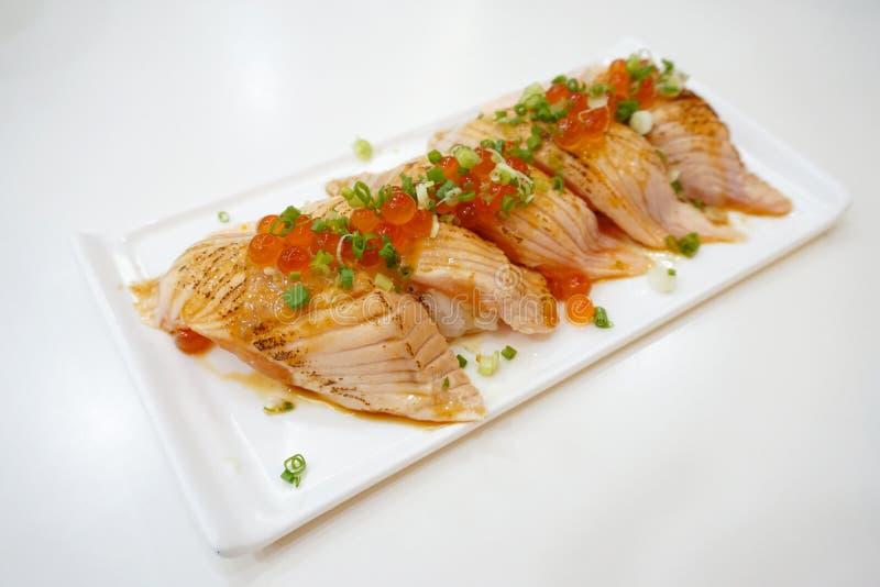 Primo piano dei sushi di color salmone su un piatto bianco con le uova di color salmone e la cipolla di inverno tagliata fotografia stock