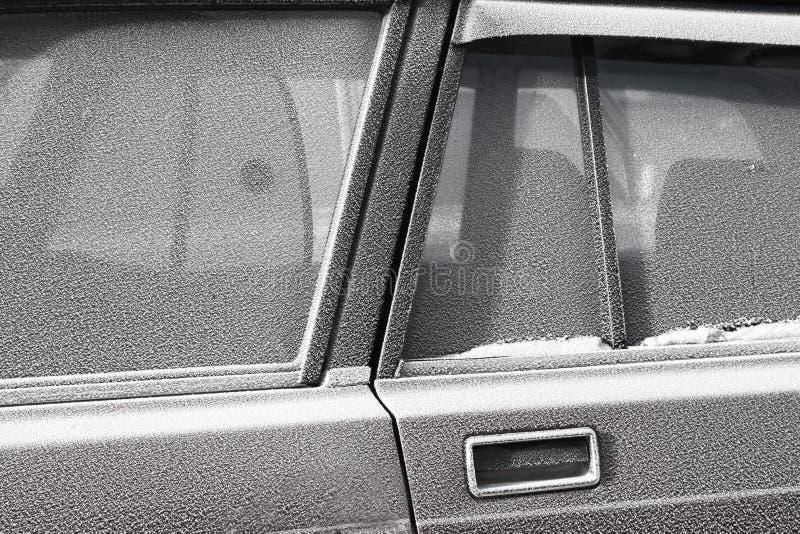 Primo piano dei tergicristalli e del parabrezza glassato dell'automobile coperti di ghiaccio e di neve monocromatico fotografia stock