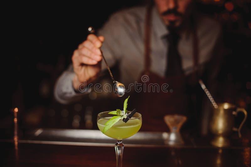 Primo piano del barista che fa cocktail verde immagine stock
