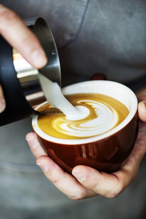Primo piano del barista che produce il caffè di arte del latte bere immagine stock libera da diritti