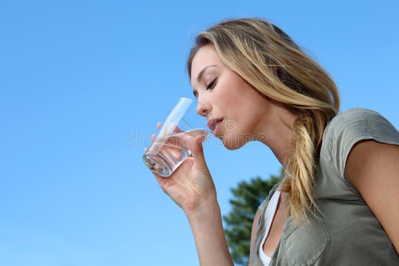 Primo piano del bicchiere biondo della giovane donna di acqua immagini stock libere da diritti