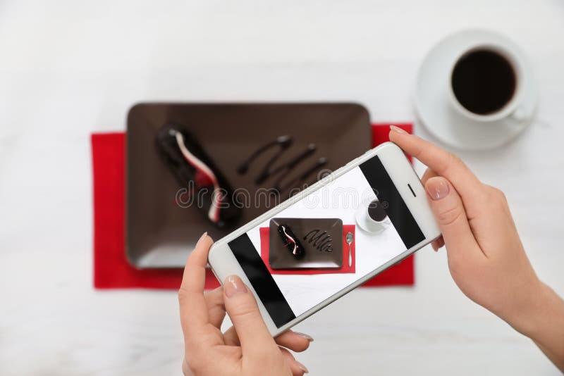 Primo piano del blogger dell'alimento che fotografa dessert e caffè saporiti con il telefono cellulare fotografie stock