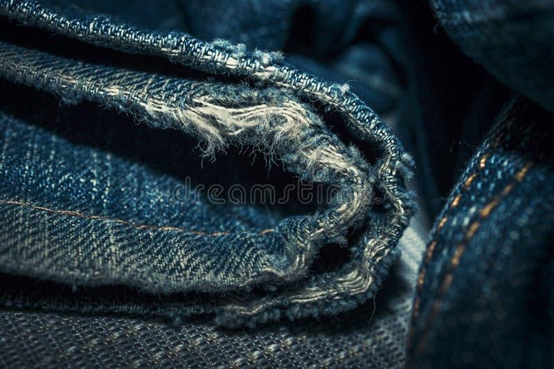 Primo piano del bordo inferiore sfilacciato dell'apertura della gamba delle blue jeans del denim fotografie stock libere da diritti