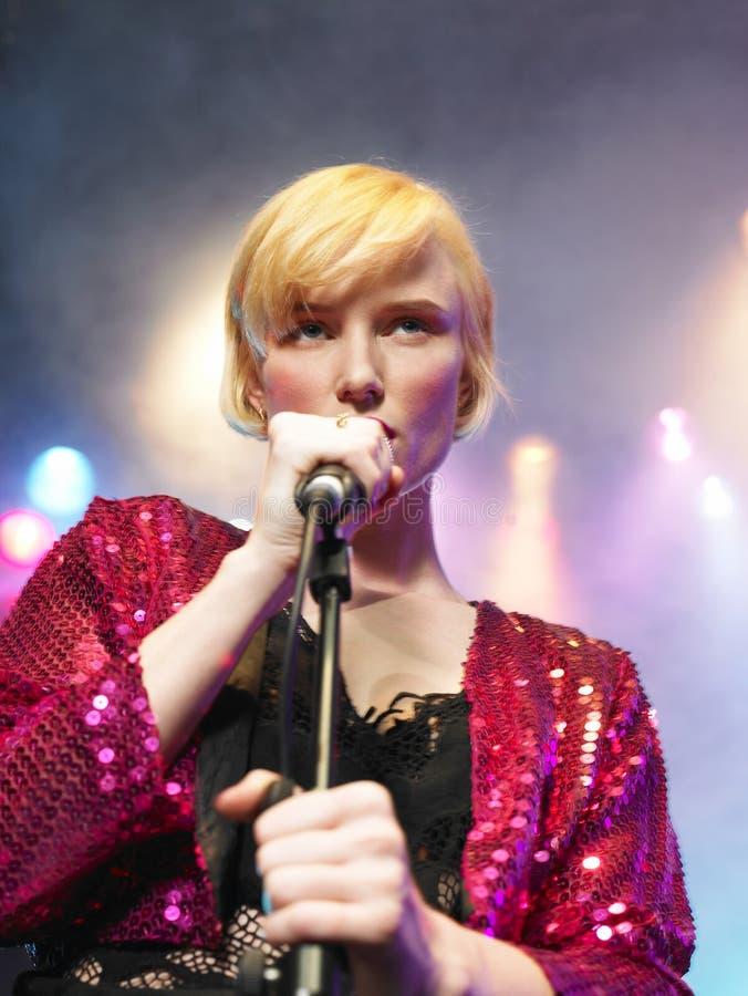 Primo piano del canto della giovane donna nel microfono immagini stock libere da diritti