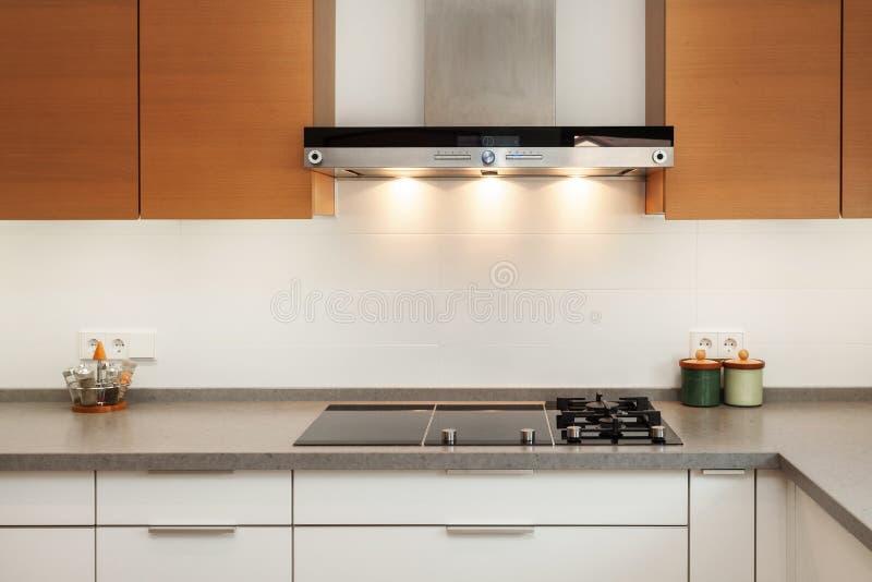 Primo piano del cappuccio dello scarico e del piatto di cottura ceramico nella nuova cucina moderna fotografie stock libere da diritti