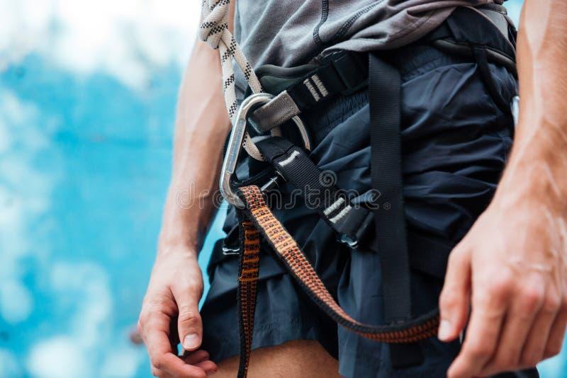 Primo piano del cavo di sicurezza d'uso dello scalatore e dell'attrezzatura rampicante immagini stock libere da diritti