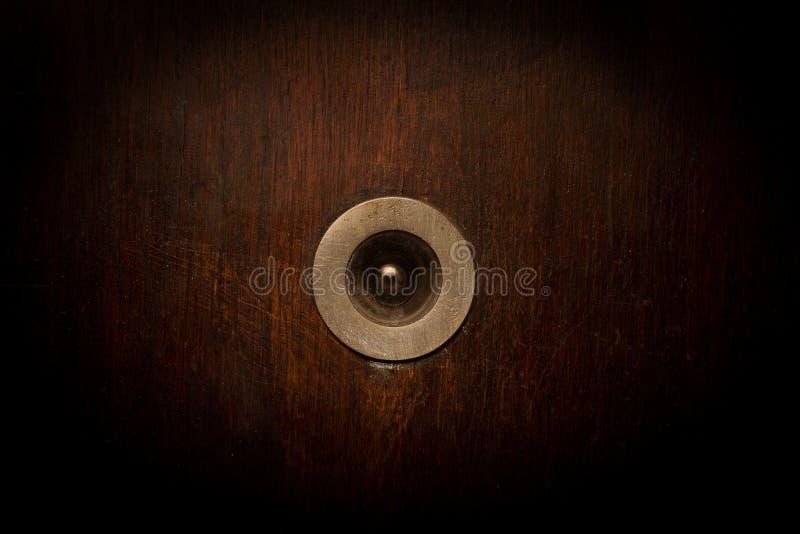 Primo piano del cercatore di vista d'annata della porta di legno fotografia stock